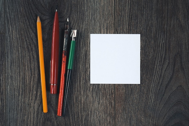 Op een donkere houten vloer zijn pennen en potloden voor kantoor, wit papier