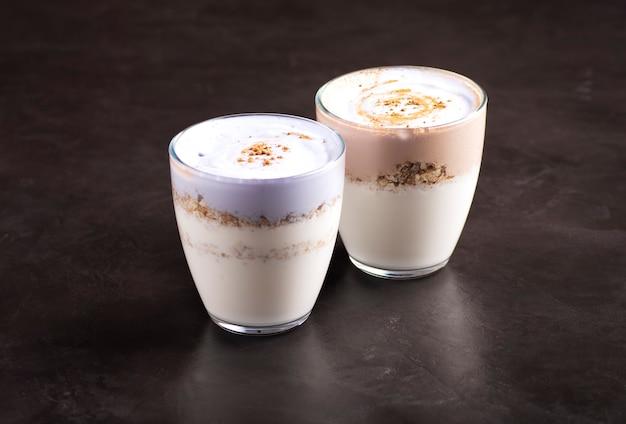 Op een donkergrijze tafel staan twee glazen huisgemaakte kefir met granola.