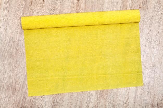 Op een eiken bord ligt een open rol golfpapier van geel.