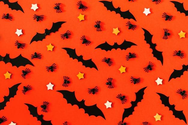 Op een fel oranje oppervlak, veel decoratieve zwarte spinnen, vleermuizen.