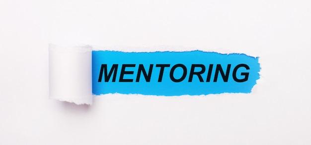 Op een felblauwe achtergrond, wit papier met een gescheurde streep en de tekst mentoring