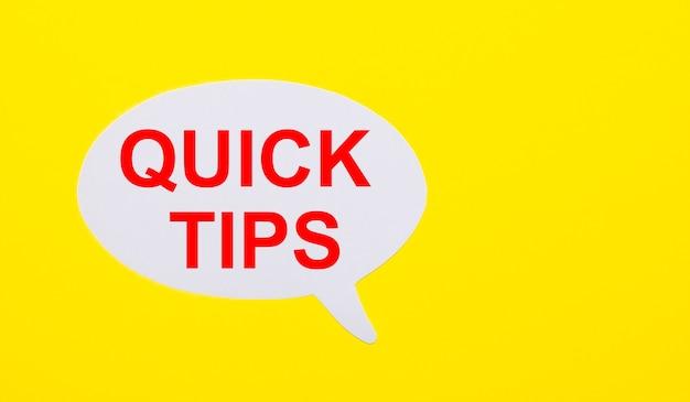 Op een felgeel oppervlak, wit papier met de woorden quick tips