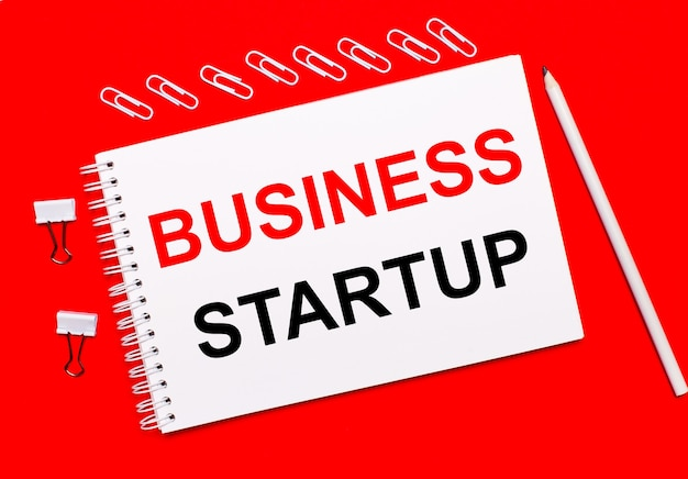 Op een felrode achtergrond, een wit potlood, witte paperclips en een wit notitieboekje met de tekst business startup