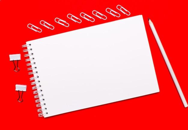 Op een felrode achtergrond een wit potlood, witte paperclips, witte paperclips en een wit blanco notitieboekje met ruimte om tekst in te voegen.