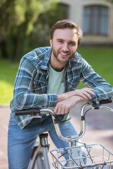 Op een fiets. een lachende man in een geruit overhemd op een fiets