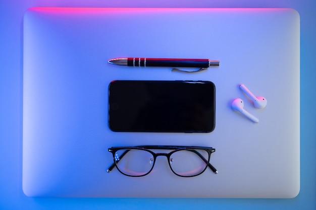 Op een gekleurde achtergrond, laptop, bril, pen, koptelefoon, bovenaanzicht. bedrijfsconcept.