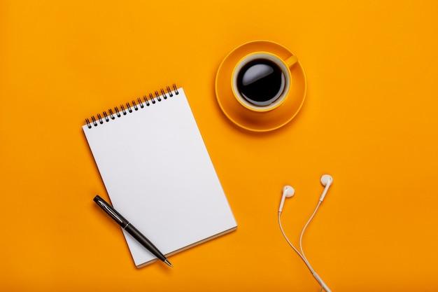 Op een gele achtergrond, een kopje zwarte koffie met een notitieblok en een koptelefoon