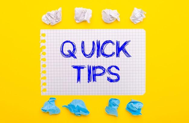 Op een gele achtergrond, wit en blauw verfrommelde stukjes papier en een notitieboekje met de tekst quick tips.