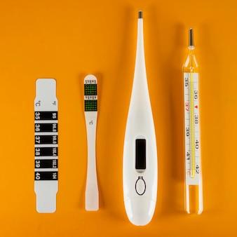 Op een gele achtergrond zijn er vier soorten thermometers: vloeibaar kristal, klinisch, elektrisch en kwik. concept van gezondheidszorg en geneeskunde.