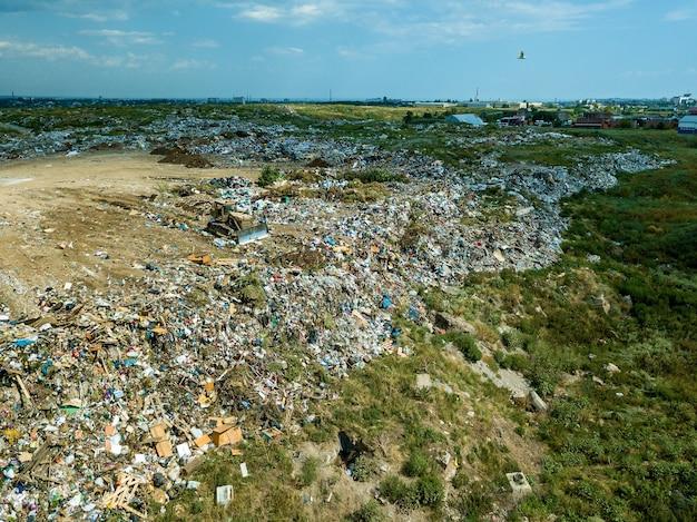 Op een gemeentelijke stortplaats duwt een bulldozer-tractor afval van een berg afval. milieuschade, ecologie bedreigd