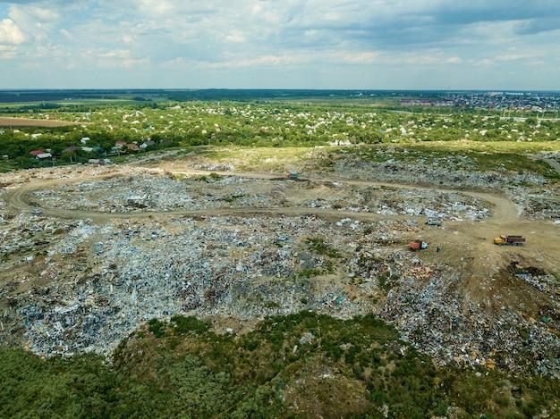 Op een gemeentelijke stortplaats duwt een bulldozer-tractor afval van een berg afval