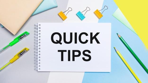 Op een grijs en blauw oppervlak zijn briefpapier van geelgroene kleur, een notitieboekje met de tekst quick tips. plat leggen.