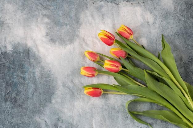 Op een grijze achtergrond een boeket van tulpen. vrije ruimte voor tekst