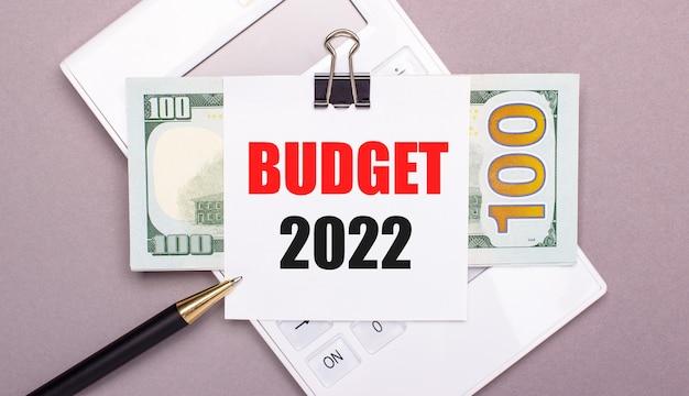 Op een grijze achtergrond, een witte rekenmachine, een pen, bankbiljetten en een vel papier onder een zwarte paperclip met de tekst budget 2022. bedrijfsconcept