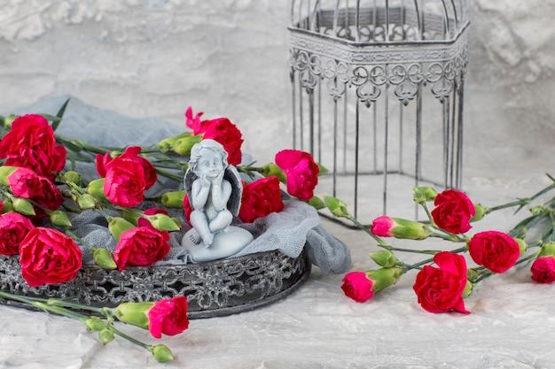 Op een grijze achtergrond heldere anjers op een grijs dienblad, een kooi en een figuur van een engel