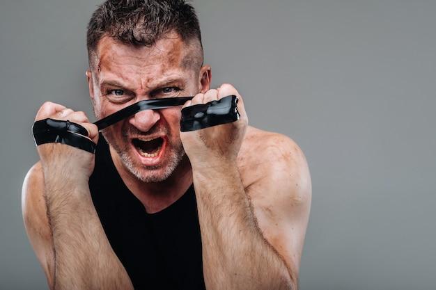 Op een grijze achtergrond staat een gehavende man in een zwart t-shirt die eruitziet als een vechter en zich voorbereidt op een gevecht