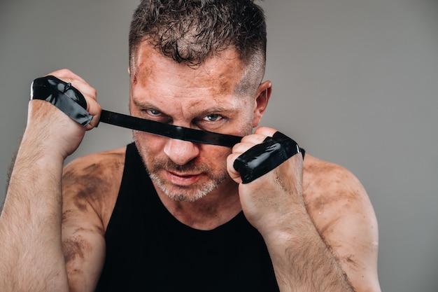 Op een grijze achtergrond staat een gehavende man in een zwart t-shirt die eruitziet als een vechter en zich voorbereidt op een gevecht.