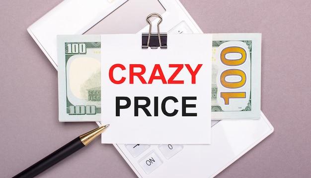 Op een grijze achtergrond staat een witte rekenmachine, een pen, contant geld en een stuk papier onder een zwarte paperclip met de tekst crazy price. bedrijfsconcept