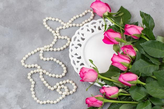 Op een grijze betonnen achtergrond een boeket van roze rozen, een bord en parel kralen