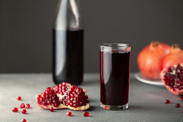 Op een grijze betonnen tafel staat een fles glas met granaatappelsap. in de buurt zijn verschillende plakjes granaatappels.