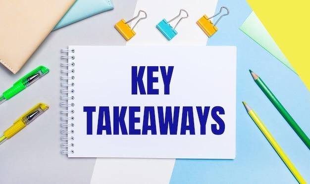 Op een grijze en blauwe achtergrond staan briefpapier van geel-groene kleur, een notitieboekje met de tekst key takeaways. plat leggen.