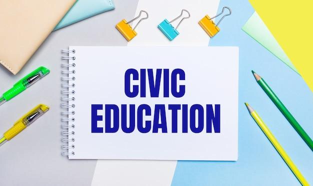 Op een grijze en blauwe achtergrond staan briefpapier van geelgroene kleur, een notitieboekje met de tekst civic education. plat leggen.