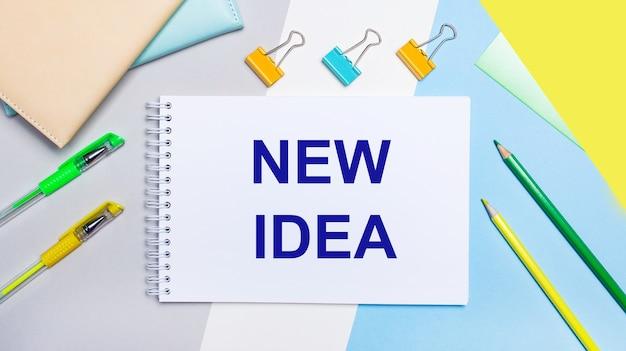 Op een grijze en blauwe achtergrond staan briefpapier van geelgroene kleur, een notitieboekje met de tekst new idea. plat leggen.