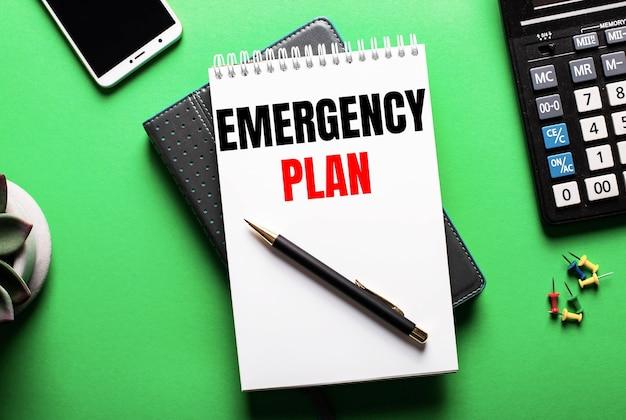 Op een groene achtergrond - een telefoon, een rekenmachine en een dagboek met het opschrift emergency plan