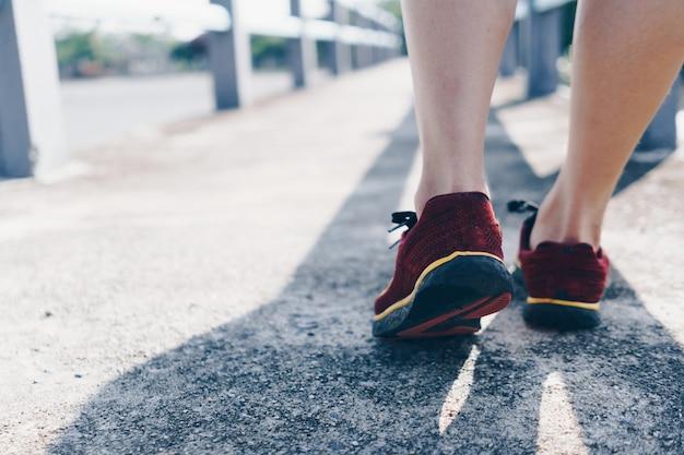 Op een groene achtergrond loopt en rent een vrouw terwijl ze hardloopschoenen draagt. lichaamsbeweging voor de gezondheid is een begrip.