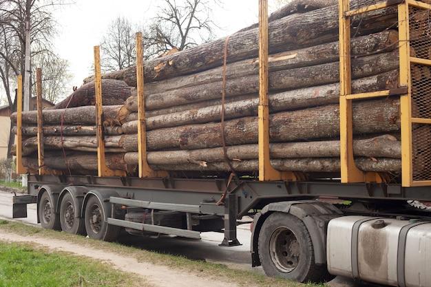 Op een grote speciale machine liggen stammen van verschillende diktes. de steigerbouwer staat langs de kant van de weg.