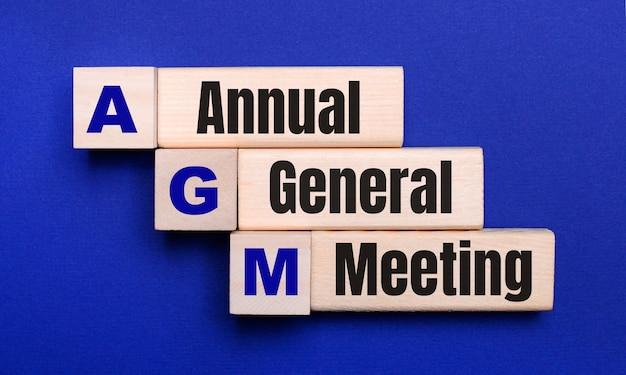 Op een helderblauwe achtergrond, lichte houten blokken en kubussen met de tekst agm annual general meeting.