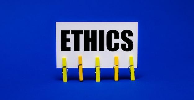 Op een helderblauwe ondergrond op gele wasknijpers een witte kaart met de tekst ethics