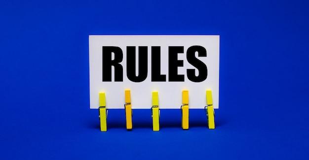 Op een helderblauwe ondergrond op gele wasknijpers een witte kaart met de tekst regels