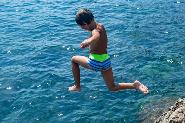 Op een hete zomerdag springt een jongen van de klif de zee in. vakantie op het strand. het concept van actief toerisme en recreatie