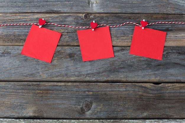 Op een houten achtergrond, een touw en daarop op wasknijpers rode notitie papier