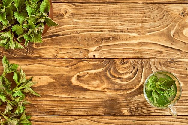 Op een houten achtergrond is een glas met gebrouwen jonge brandnetels. medicinale bouillon van brandnetel. vitamine kruidenthee. tinctuur van brandnetel. het uitzicht vanaf de top