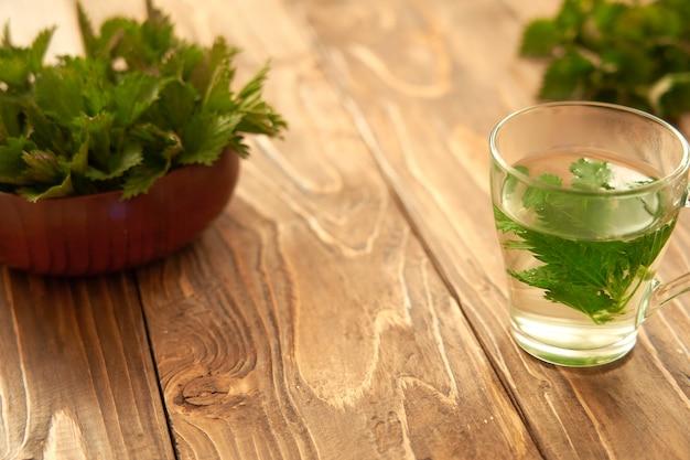 Op een houten achtergrond is een glas met gebrouwen jonge brandnetels. medicinale bouillon van brandnetel. vitamine kruidenthee.