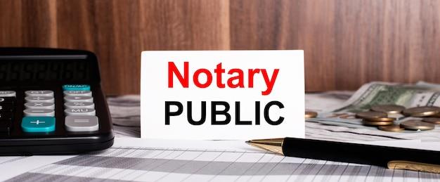 Op een houten achtergrond ligt pen met rekenmachine en witte kaart met woorden notaris publiek