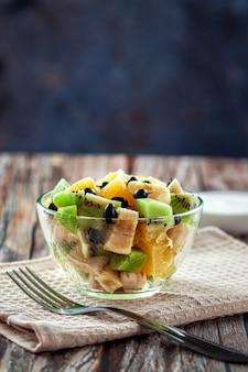 Op een houten achtergrond, verse fruitsalade voor een gezond dieet