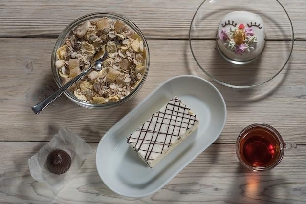 Op een houten achtergrondchocolade, kinderentaart, een kop thee en muesli met gedroogd fruit
