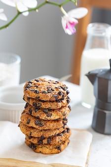 Op een houten bord liggen amerikaanse koekjes met stukjes chocolade