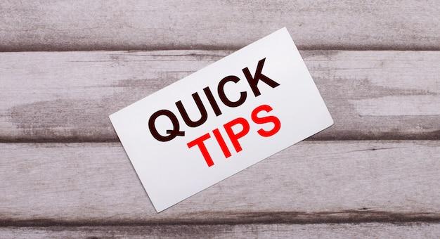 Op een houten ondergrond ligt een witte kaart met de rode tekst quick tips
