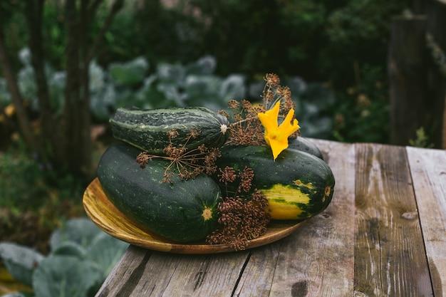 Op een houten schaal liggen verse courgettes uit eigen tuin.