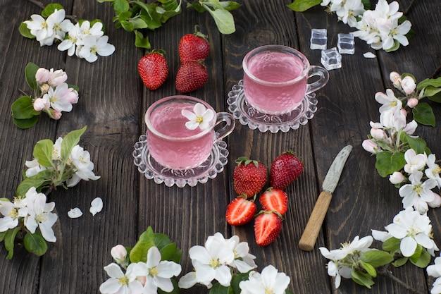 Op een houten tafel aardbeien, ijs, een drankje in mokken, witte bloemen