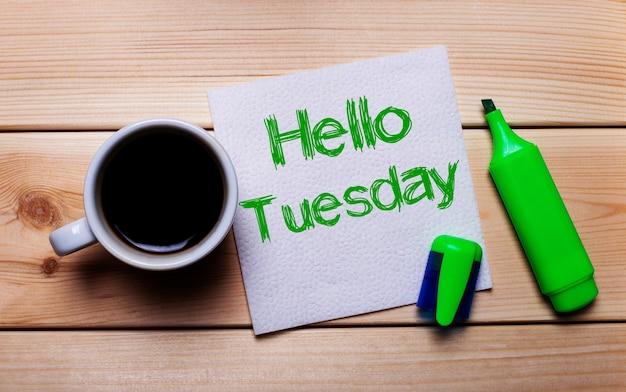 Op een houten tafel een kopje koffie, een groene stift en een servet met de tekst hello dinsdag