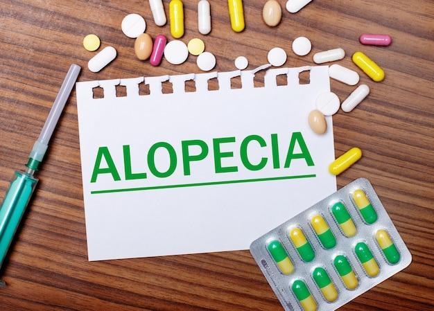 Op een houten tafel, een spuit, pillen en een vel papier met de inscriptie alopecia. medisch concept