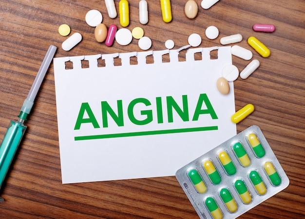 Op een houten tafel, een spuit, pillen en een vel papier met de inscriptie angina. medisch concept