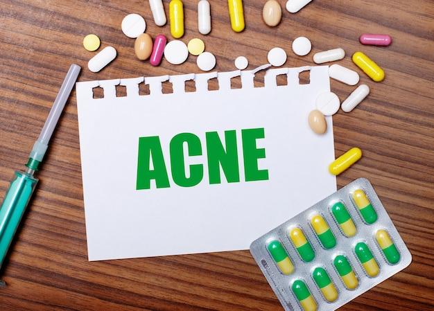 Op een houten tafel, een spuit, pillen en een vel papier met het opschrift acne. medisch concept