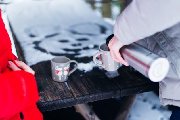 Op een houten tafel, gedeeltelijk bedekt met sneeuw, staan twee kopjes en een man schenkt een warm drankje voor hen in