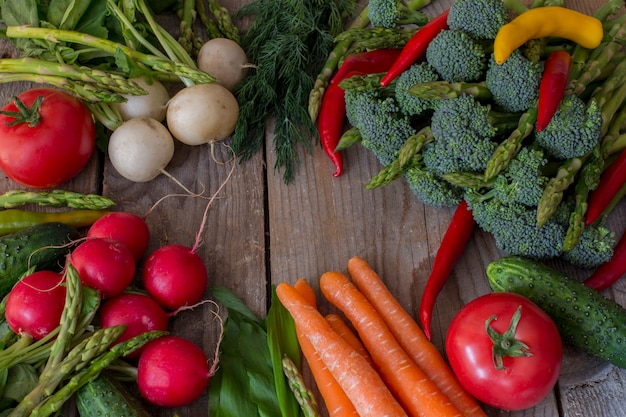 Op een houten tafel groenten asperges, broccoli, chili peper, radijs, wortelen, tomaten
